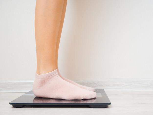 As pernas femininas em meias estão em uma balança elétrica contra uma parede branca.