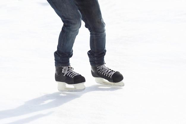 As pernas montam um cara patinando na pista de gelo. esporte e entretenimento. descanso e férias de inverno.