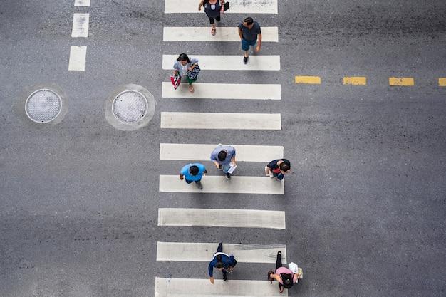 As pessoas andam na rua na cidade ao longo da estrada de tráfego de passagem para pedestres