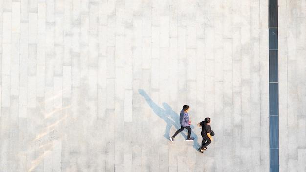 As pessoas andam na sombra de silhueta preta de pedestres paisagem concreta no chão