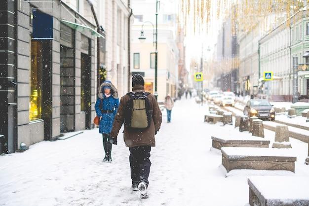 As pessoas andam nas ruas da cidade sob a neve b