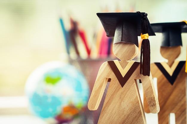 As pessoas assinam madeira com graduação comemorando cap no livro aberto com modelo global mapa
