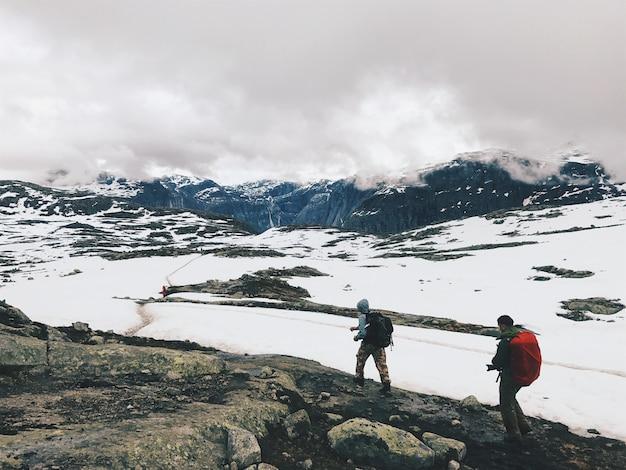 As pessoas atravessam as montanhas cobertas de neve