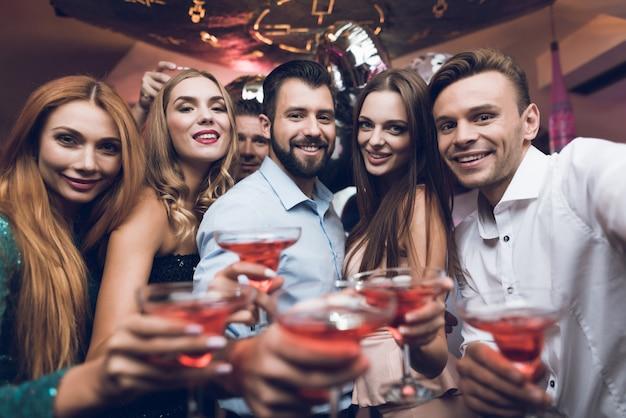 As pessoas bebem coquetéis e se divertem na boate.