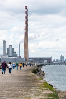 As pessoas caminham em sua grande caminhada para o sul, no farol de pollbeg.