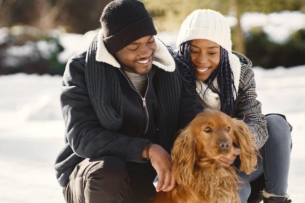 As pessoas caminham lá fora. dia de inverno. casal africano com cachorro.