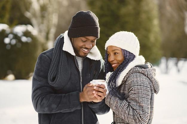 As pessoas caminham lá fora. dia de inverno. casal africano com café.