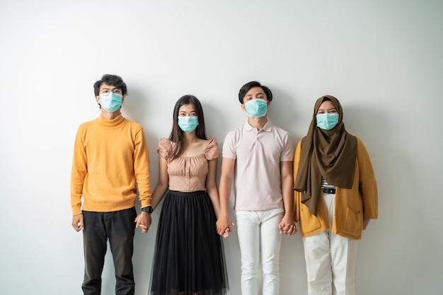 As pessoas com máscaras de rosto seguram a mão
