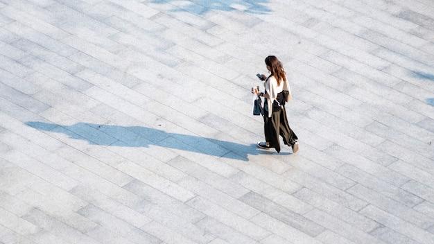 As pessoas com vista aérea superior atravessam o concreto para pedestres com sombra negra na silhueta,