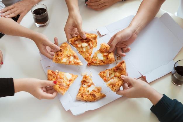 As pessoas comem fast food. mãos de amigos pegando fatias de pizza