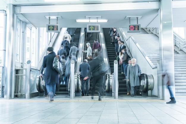 As pessoas correm em um movimento de escada rolante turva