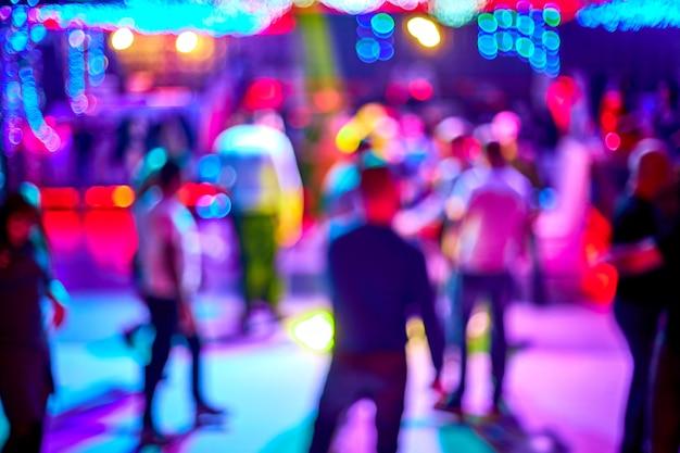 As pessoas dançam, cantam, se divertem e relaxam em uma boate turva.