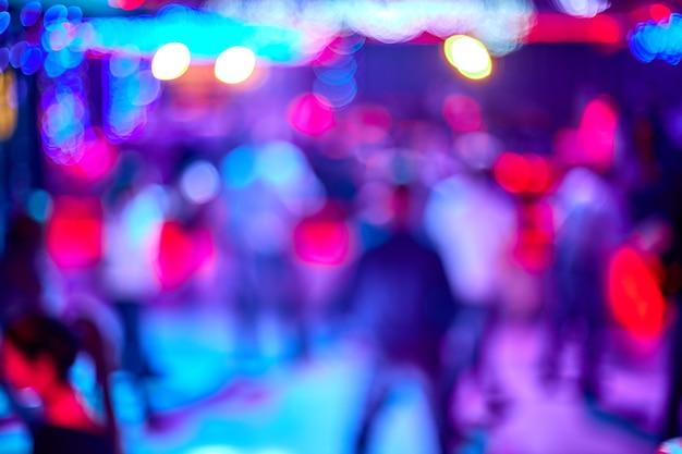 As pessoas dançam, cantam, se divertem e relaxam no fundo desfocado da boate. flashes de luz lindas luzes desfocadas na pista de dança