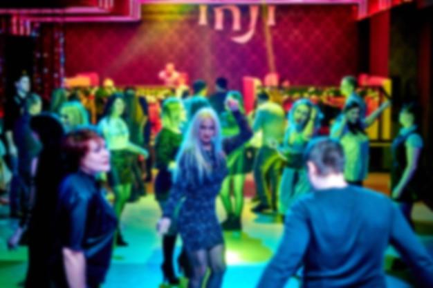 As pessoas dançam na pista de dança da boate, muita gente. luzes estroboscópicas brilhantes