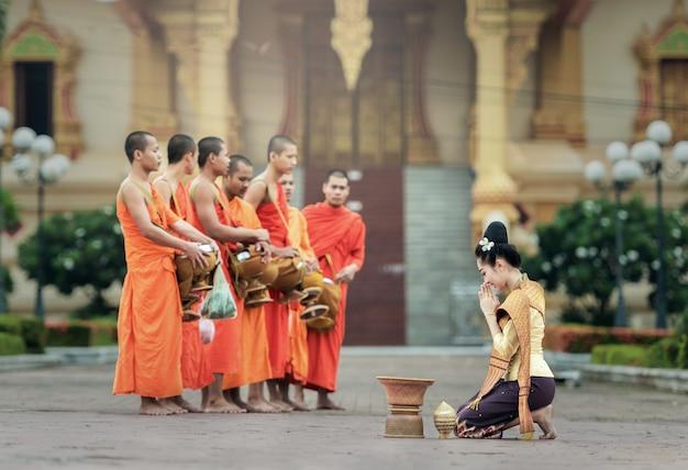 As pessoas dão oferendas de comida aos monges budistas em vientiane, laos.