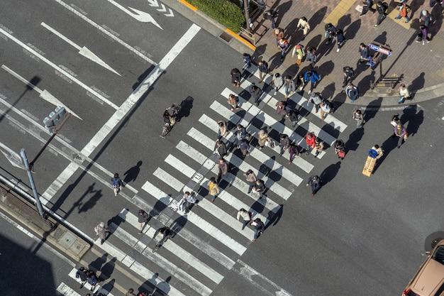 As pessoas de vista superior que andam ultrapassam a faixa de travessia de interseção de rua