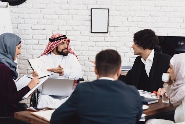 As pessoas discutem gráfico de relatório de negócios e tabelas