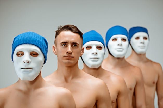 As pessoas em máscaras e um homem sem máscara