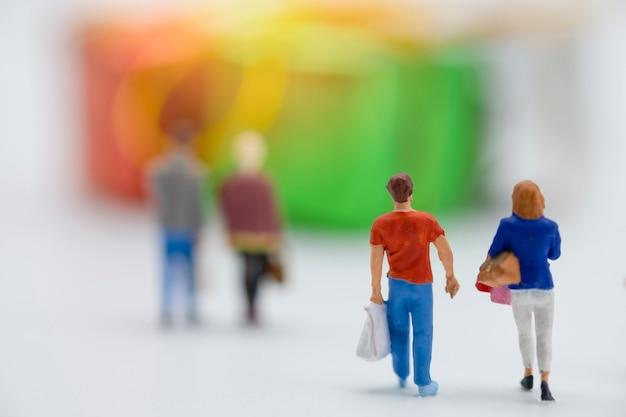 As pessoas em miniatura compram mercadorias ou mercadorias durante a grande venda e desconto