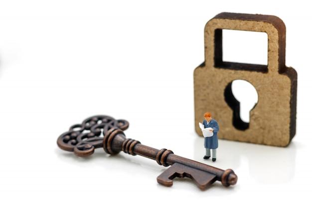 As pessoas em miniatura leem o livro para descobrir como desbloquear a chave, educação ou conceito de negócio.