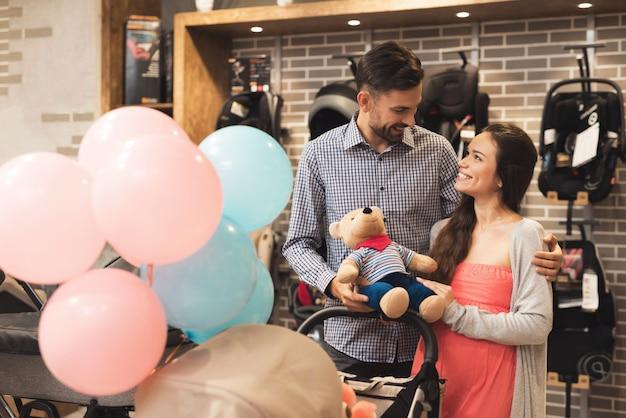 As pessoas escolhem um carrinho de bebê.