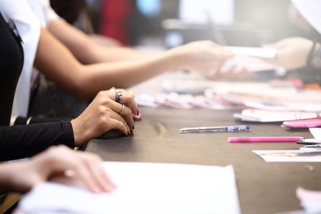 As pessoas escrevem o formulário de inscrição e enviam o documento para a entrevista de emprego