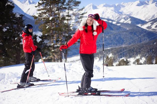 As pessoas esquiam montanhas alpinas com neve branca e céu azul