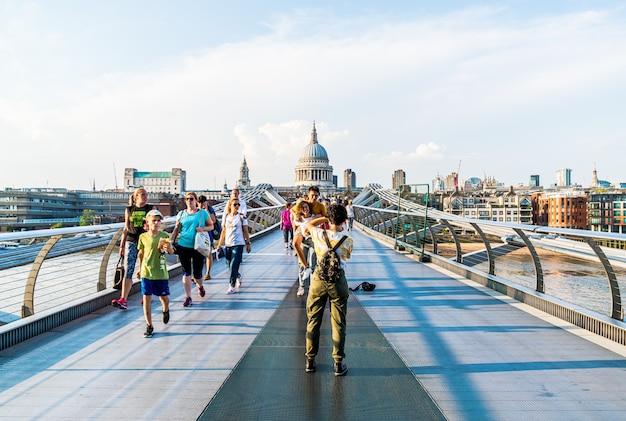 As pessoas estão caminhando pela ponte millenium