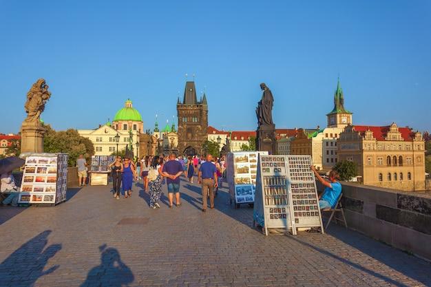 As pessoas estão caminhando sobre a famosa ponte carlos em praga.
