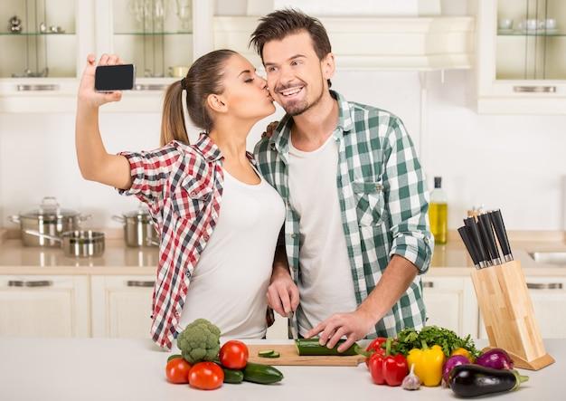 As pessoas estão cozinhando, beijando e tirando uma foto.
