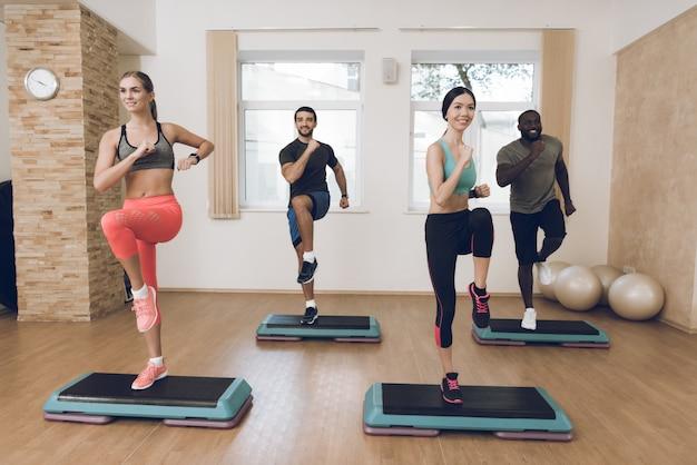 As pessoas estão envolvidas em fitness no ginásio moderno com amigos