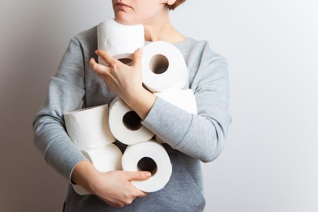 As pessoas estão estocando papel higiênico. mulher segura muitos rolos de papel higiênico