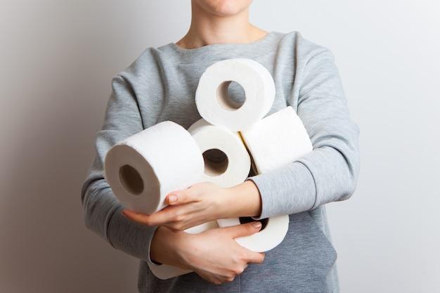 As pessoas estão estocando papel higiênico para quarentena em casa contra o coronavírus. mulher segura muitos rolos de papel higiênico