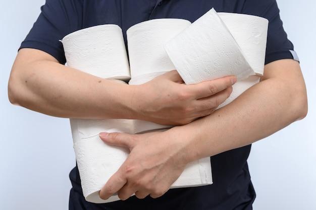 As pessoas estão estocando papel higiênico para quarentena em casa contra o coronavírus. um homem segura muitos rolos de papel higiênico.