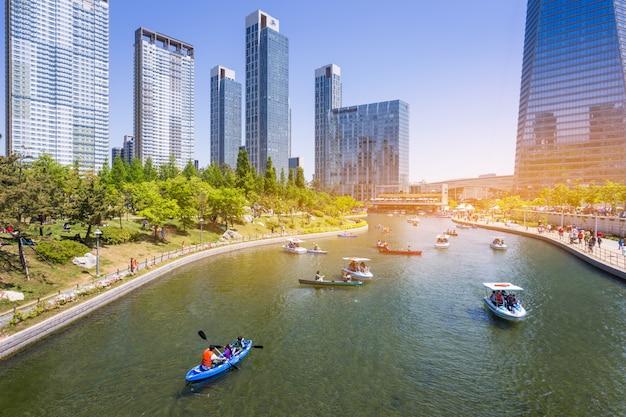 As pessoas estão montando um barco turístico no verão da coréia no central park, no distrito de songdo, incheon, coréia do sul.