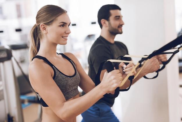 As pessoas estão no ginásio e se concentram nos exercícios difíceis.