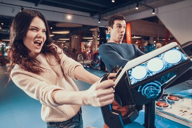 As pessoas estão pilotando aeronaves jogando no arcade