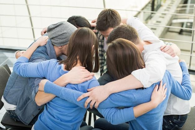 As pessoas estão sentadas abraçando em círculo e apoiando.
