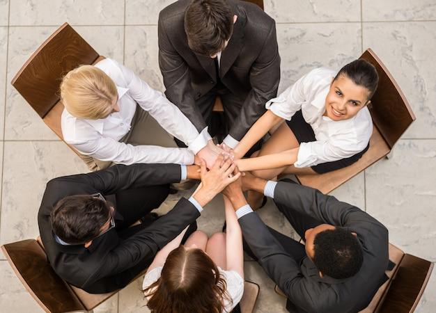 As pessoas estão sentadas em círculo e juntando as mãos.