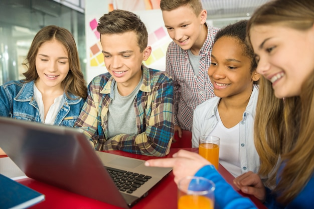As pessoas estão usando o laptop e bebendo suco de laranja.