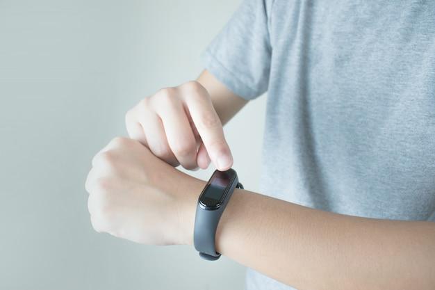 As pessoas estão usando um relógio inteligente para verificar a freqüência cardíaca.