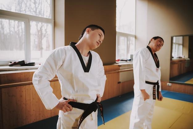 As pessoas fazem exercícios de aquecimento antes de iniciar o kung fu.