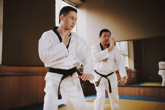 As pessoas fazem exercícios de aquecimento antes de iniciar o treinamento de karatê.