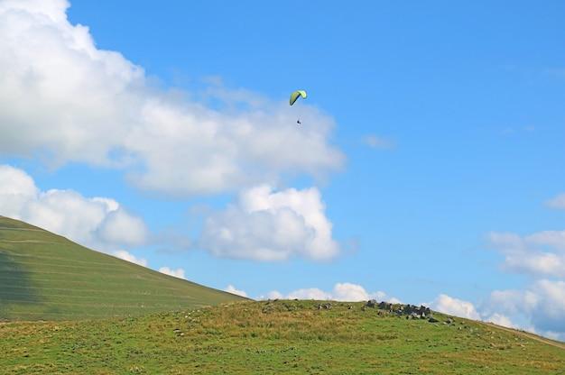 As pessoas gostam de voar de parapente sobre o exuberante pico das montanhas do cáucaso, geórgia