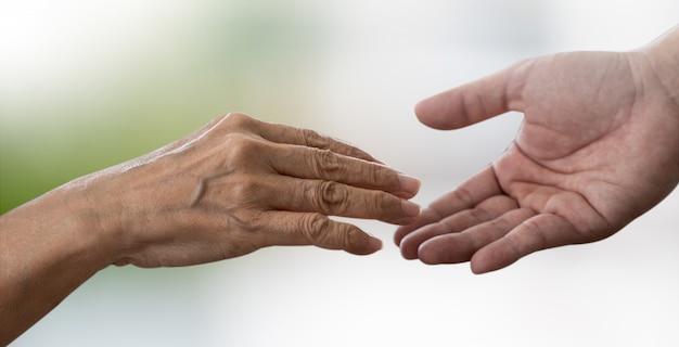 As pessoas idosas e as mãos jovens cuidam de cuidados de saúde desativado andando com assistência