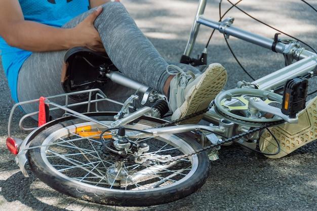 As pessoas lá estão com uma lesão no joelho quando a bicicleta cai ao andar dentro do parque