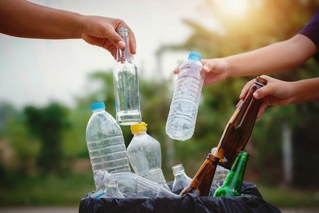 As pessoas mão segurando a garrafa de lixo de plástico e vidro, colocando em saco de reciclagem para limpeza