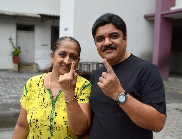 As pessoas mostram seus dedos marcados com tinta depois de votarem