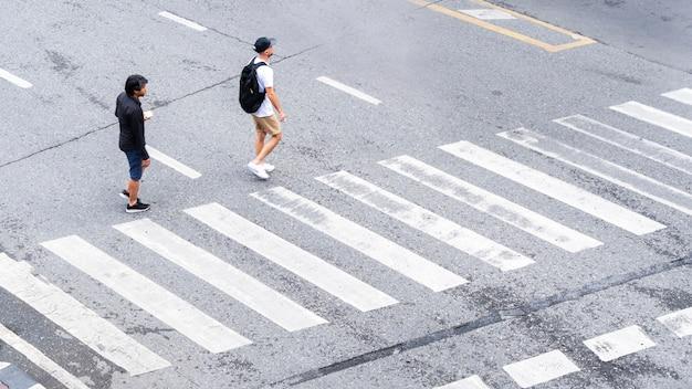As pessoas movimentadas da cidade passam para a faixa de pedestres na estrada de tráfego comercial.