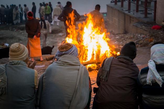 As pessoas olham para a pira funerária naquela noite. a cerimônia da cremação de manikarnika ghat nas margens do rio ganges em varanasi, índia.
